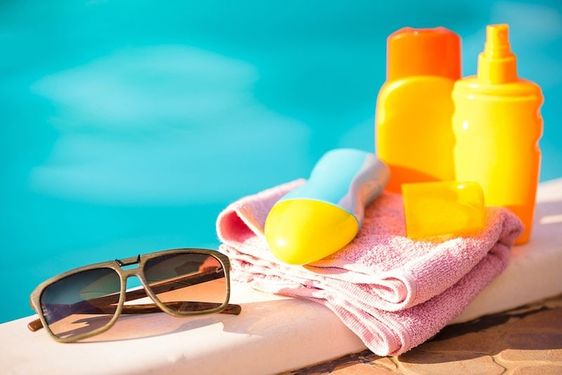 Sunglasses and sunscreen by a pool in Milford, Ohio, where an air conditioning unit is blowing hot air.