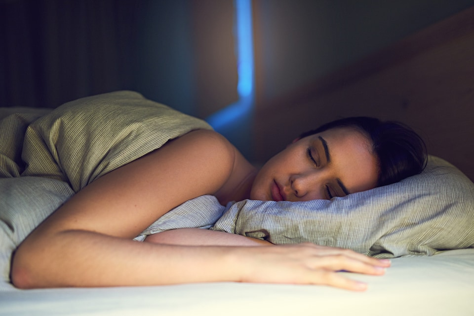woman resting comfortably after gaining health benefits from sleeping while using her AC