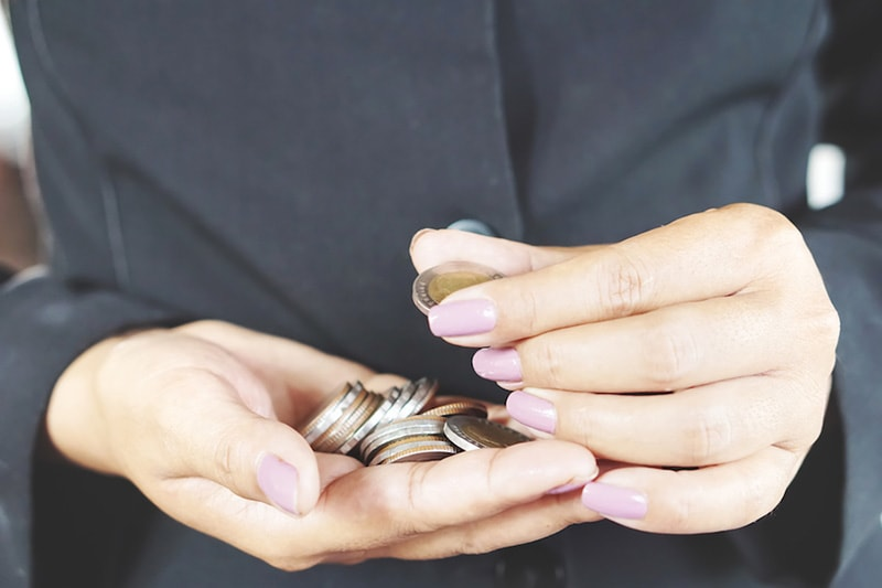 Woman counting coins in hand, How Can I Afford a New AC System & HVAC Equipment? | Miford, OH