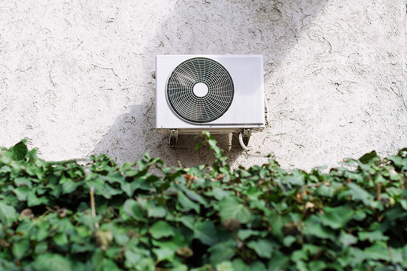 An air conditioner on the outside of building showing one of the many ways your central air conditioner can cool your home.