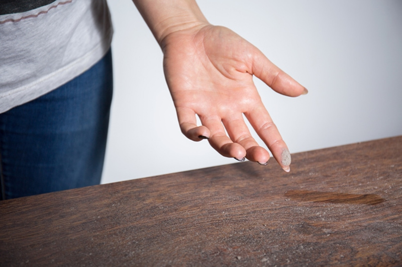 Woman wiping dust off her table with her finger and wondering how to help eliminate dust in her home.