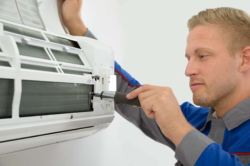 Do I Really Need an AC Tune-Up? Portrait Of Young Male Technician Repairing Air Conditioner